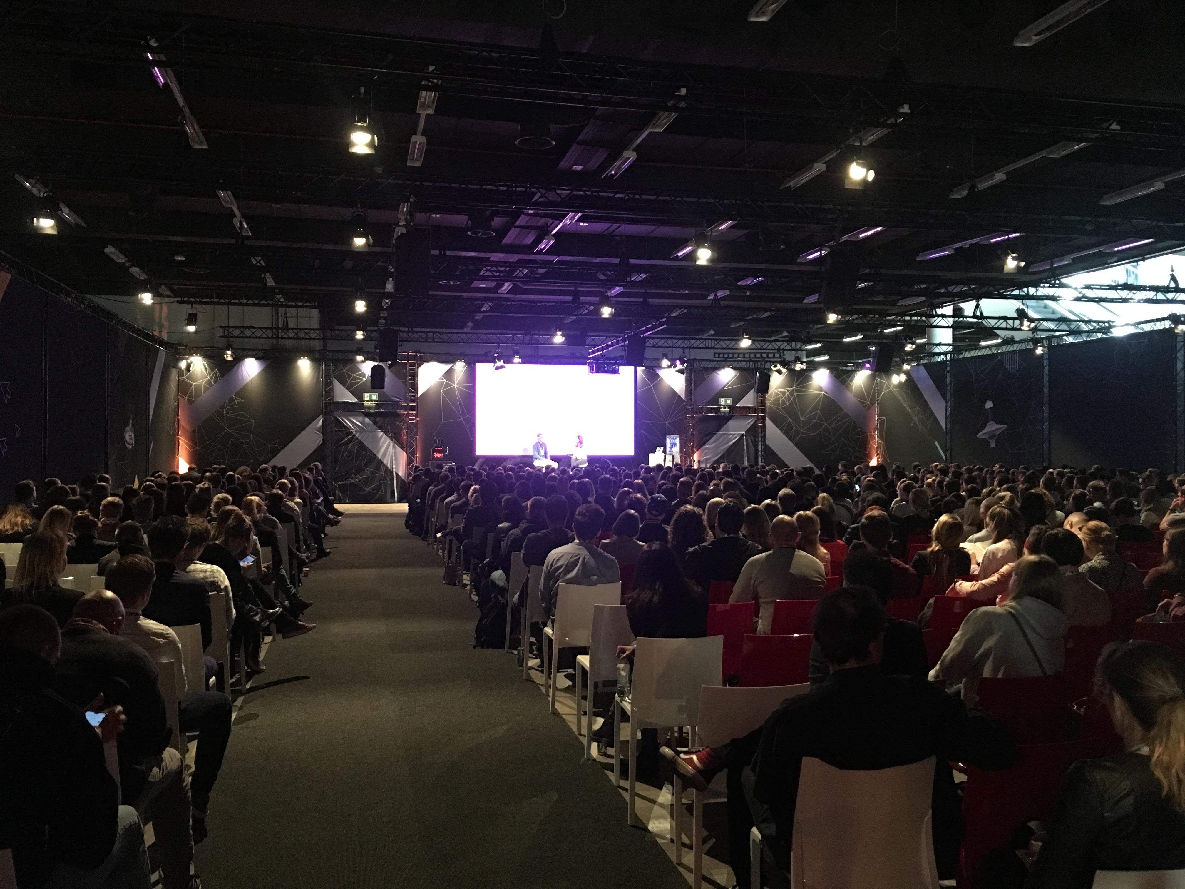 Foto do evento OMR Festival. Platéia com muitas pessoas sentadas e no fundo um telão e o palco do evento. No palco duas pessoas sentadas em cadeiras.