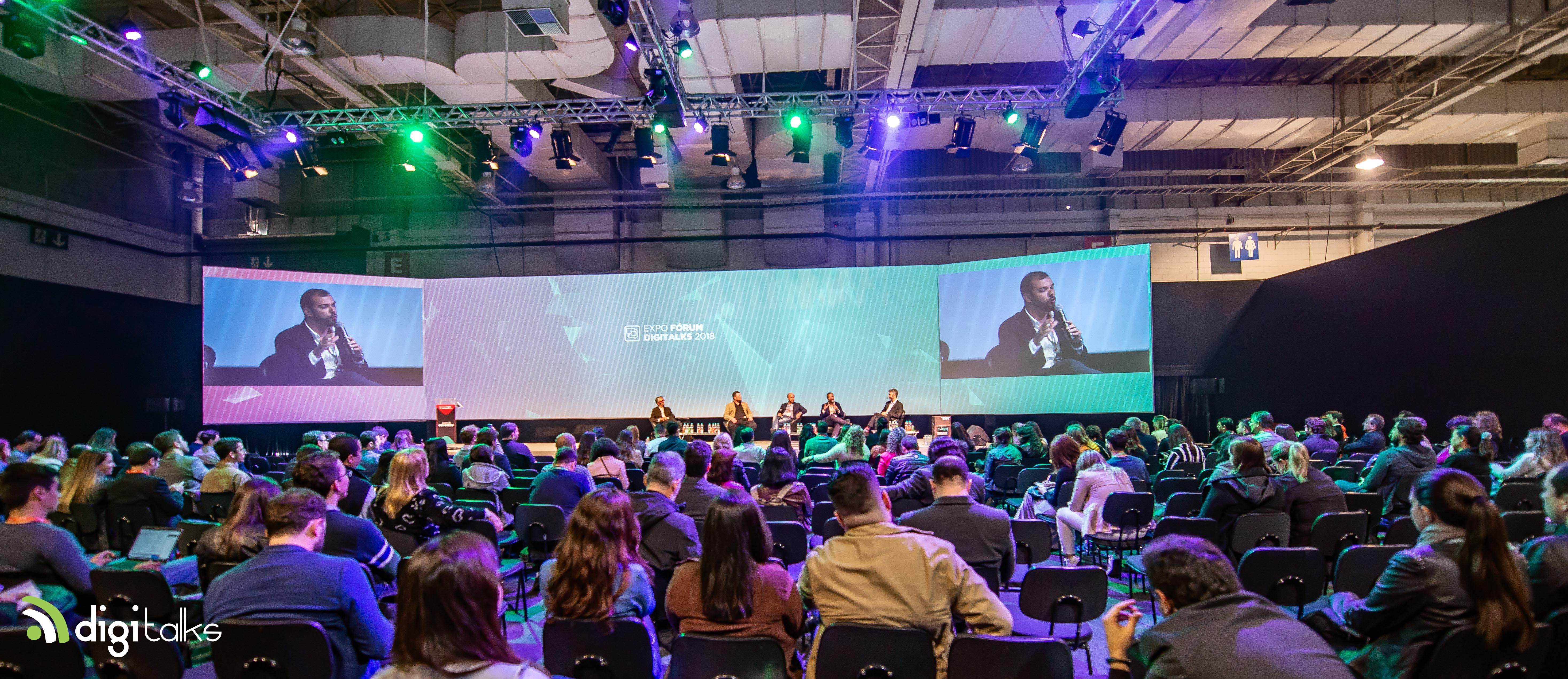 Foto. Platéia do Expo Digitalks está sentada em cadeiras. Ao fundo um grande telão e um palco. Em cima do palco estão alguns palestrantes do evento.