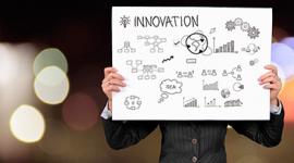 Foto: homem de te segurando um placa com a palavra Inovação.
