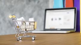Imagem: notebook aberto com um mini carrinho de compras.