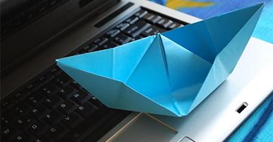Imagem: notebook com um barco de papel. revolução tecnológica.