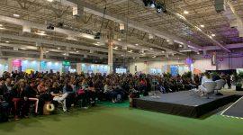 Foto: palestrantes no palco falando sobre transformação digital.
